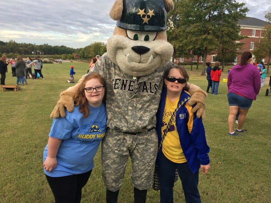Olivia Gaston and Meghan Roeder pose with a mascot at the Down Syndrome Association of West Tennessee's annual Buddy Walk in Jackson, Tenn. on October 21, 2017.