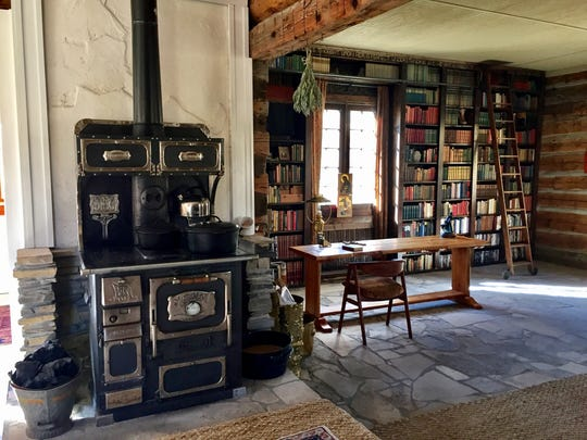 Jessie Ferguson uses a coal-burning stove at her off-the-grid restored homestead. She also opened up the building into one large room.