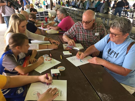 Unitarian Universalist Fellowship of Murfreesboro members making button badges for the peaceful #MurfreesboroLoves counter-protest are, clockwise from left, Allie Becker, Raleigh Giles and mom Ashley Giles, and Tom and Anna Deck.