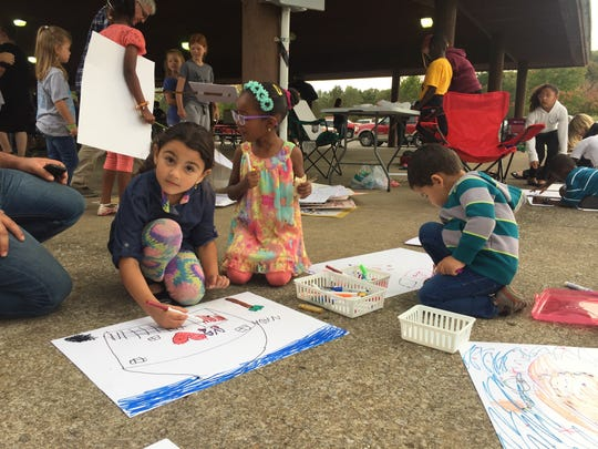 At the Love Your Neighbor Picnic on Oct. 22, 2017, from left, Nada Alzoubi, Sarrah Omer and Rashed Alzoubi make posters in preparation to counter the hate messages being brought Oct. 28 by the League of the South White Lives Matter.