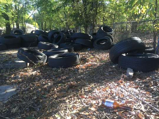 Tires dumped illegally in the vacant lot beside a number