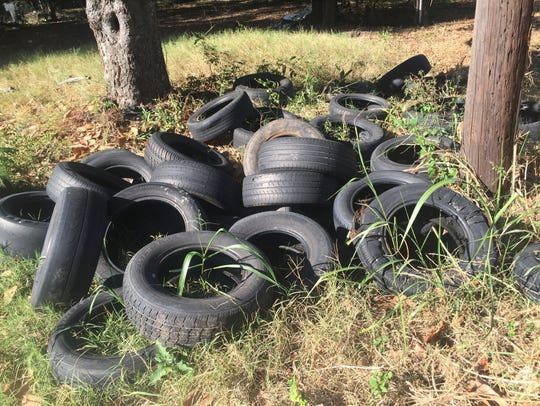 Tires dumped illegally near a residential area in the