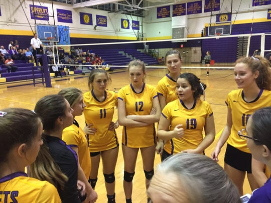 The Byrd volleyball team huddles during a timeout against