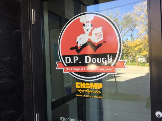 The Chomp logo is seen at the front door of D.P. Dough in Iowa City on Oct. 25, 2017.