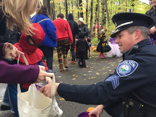 Port Huron Police Sgt. Brian Kerrigan hands out treats at the Halloween Stroll on Saturday, Oct. 28, 2017, at Sanborn Park in Port Huron.