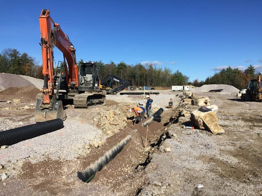 A work crew in late October lays pipe at the site of a new Rice Lumber building in Shelburne. Photographed Oct. 27, 2017.