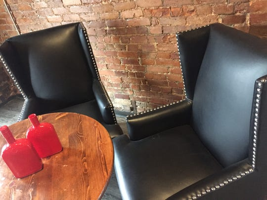 A semi-open brick wall divides the bar from an open smoking room where black leatherette wing chairs offer comfort at Stixx, a cigar bar/Asian restaurant opening at the former Bourbon Street Distillery, 361 Indiana Ave.