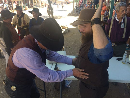 Duane Brown inspects Ed Wooden before a performance of the Goose Flats Gunslingers along Allen Street in Tombstone on Oct. 20, 2017. Brown's role as armorer and the inspections are mandated under a city ordinance.
