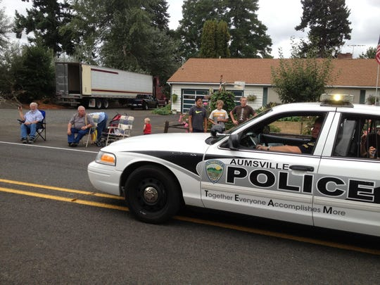 Aumsville Police cruiser fills the caboose role during the city's corn festival, Saturday, Aug. 24, 2013.