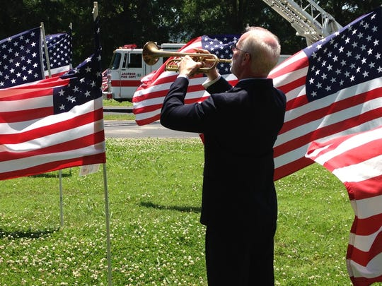 Tom Grant, a teacher at the University School of Jackson, plays taps on the trumpet to close out the Flags of Freedom dedication ceremony.