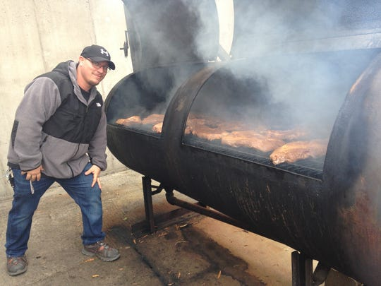 Full Service BBQ general manager David Puleo stokes the fire and inspects a smoker filled with brisket.