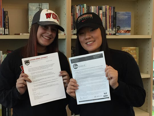 West Salem seniors Nalani Muranka (left) and Gillian Werner pose with their letters of intent after a signing ceremony at West Salem on Wednesday, Nov. 8, 2017.