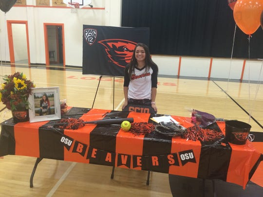 Scio softball player Ashton Phillips signs to play at Oregon State on Wednesday in the Scio gym.