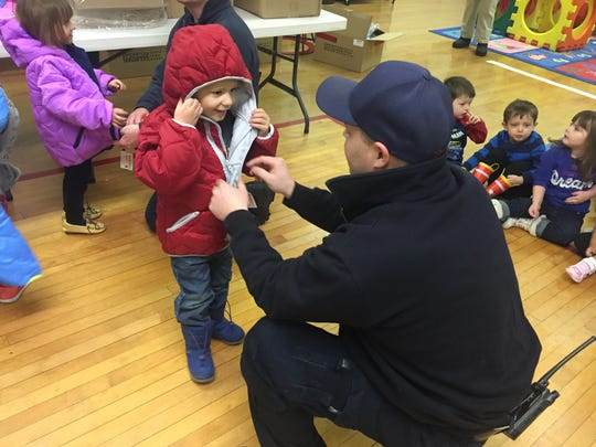 Ty Loney, engineer with Great Falls Fire Department, helps a child zip up his new coat during the Operation Warm event on Nov. 9, 2017.