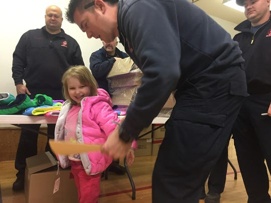 Victoria Agiotos, 4, tries on her new pink jacket during the Operation Warm event at Head Start.