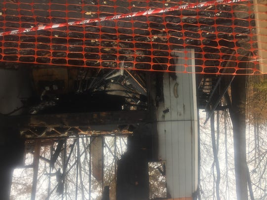 Plastic netting surrounds what is left of a home on Quaker Valley Lane in Farmington Hills after a fire.