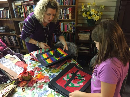 Art teacher Brooke Nowakowski sorts through paintings with Hailey Brinker, 8.