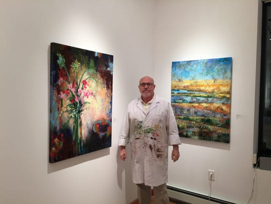Orazio Salati stands beside some of his works in his