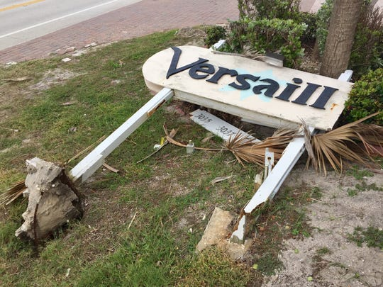 The Versailles Sur La Mer sign lies toppled on the