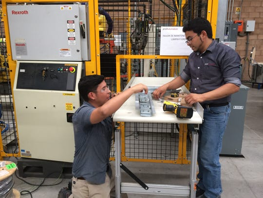 Workers at Mexican robotics company ProAutomation test