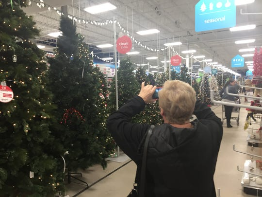 Maria Diana of Mays Landing photographs artificial trees during a visit to At Home, a decor superstore in Cherry Hill.