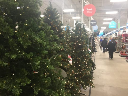 Shoppers pass a display of artificial holiday trees in the At Home store, Cherry Hill.