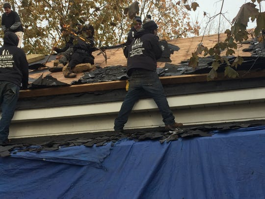 Crews work to replace the roof of Michelle Kantz's Port Huron home through the Owens Corning Roof Deployment Project.