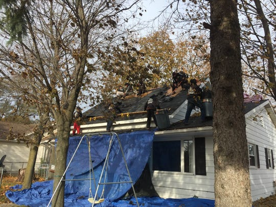 Crews work to replace the roof of Michelle Kantz's
