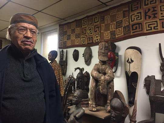Larry Miles shows some of the African art on display at his Camden bookstore and cultural center.