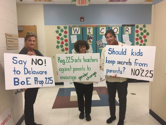 Opponents of Regulation 225 hold signs outside of the