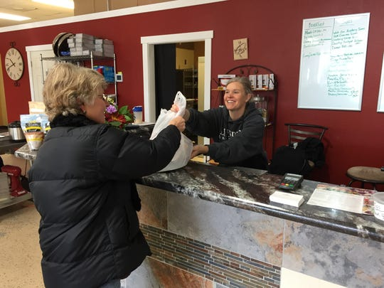 Dinners Done Right employee Angela Brewer, right, hands some ravioli to customer Gwynn Mundinger, who will serve them to her grandchildren.