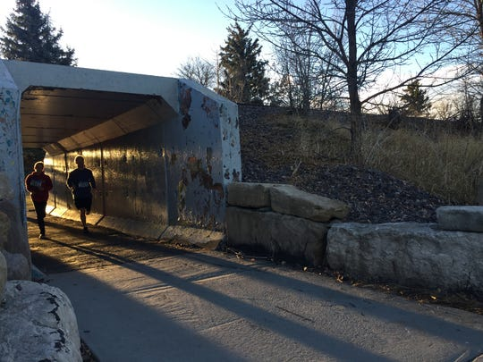 Runners race through a tunnel in Gibson Park during the 2017 Burn the Bird 5k.