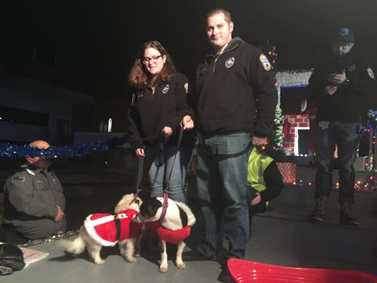 EMTs Carissa Redden and Travis McNicoll and their dogs (left-right)_ Sam and Phoebe stand on an Inspira Health Network float Friday night before the Millville Christmas Parade.