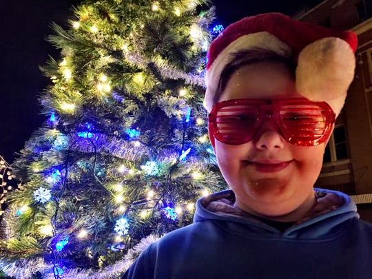 Jakob Heun, 8, rides the NeighborWorks float in the 23rd annual Festival of Lights on Saturday night.