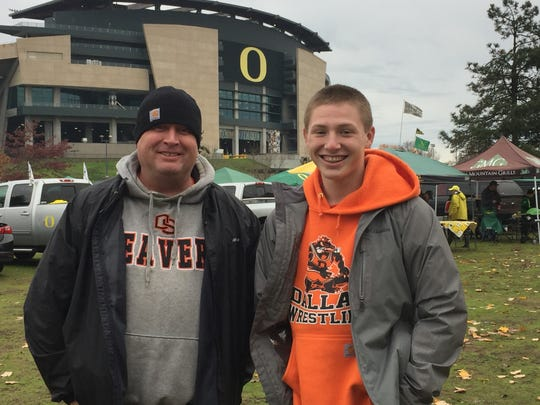 Ryan Miller (left) and his son, Bryce, from Dallas enjoy pregame festivities at the annual Civil War on Saturday at Autzen Stadium.