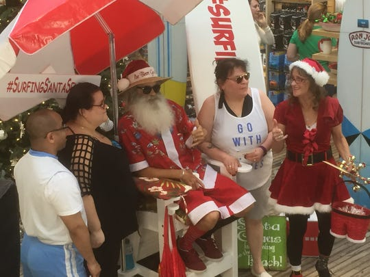 """Tourists line up in Cocoa Beach to have their photos taken with """"Surfing Santa"""" at Ron Jon Surf Shop in Cocoa Beach. Other opportunities for free photos at Ron Jon's are from 1-5 p.m. Sunday and on Dec. 6 and 17."""