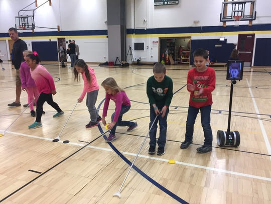 Tiernan Kriner, 8, keeps score while his classmates