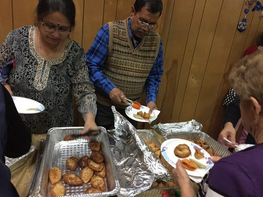 At Bharatiya Temple in Troy on Nov 30, 2017, visitors eat  Jewish and Indian foods such as potatoe latkes and samosas as seen here as part of a Hanukkah-Diwali joint celebration.