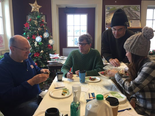 Evan Lowenstein, standing, communications and special events coordinator for the Rochester Public Market, offers a cookie to Linh Phillips at the 2016 holiday cookie contest. Adam Wilcox, left, and Michael Warren Thomas also were judges.