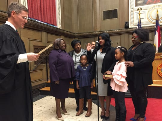 Sheneika Smith stands with family and supporters as she is sworn in by Buncombe County Superior Court Judge Alan Thorburg as one of the newest City Council members.