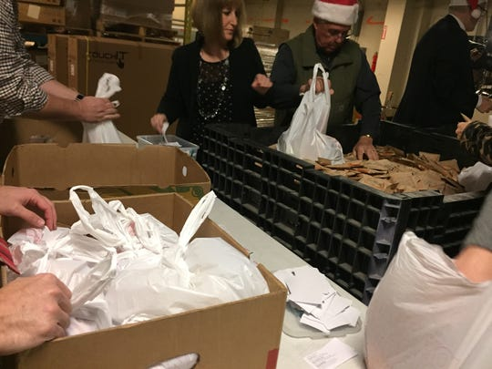 Volunteers gathered at Binghamton's East Middle School Wednesday to pack bags of food for students at risk of hunger over the holidays.