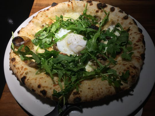 The Funghi pizza with cheese, mushrooms, a poached egg, arugula and roasted garlic from Maggie's Farm Wood-Fired Pizza in University Heights on Dec. 3, 2017.