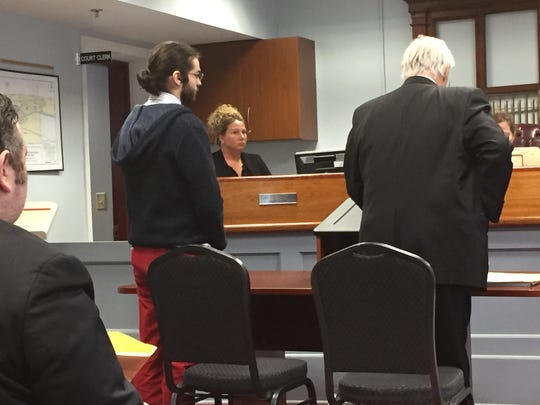 Jacob Manolt stands with his attorney during arraignment