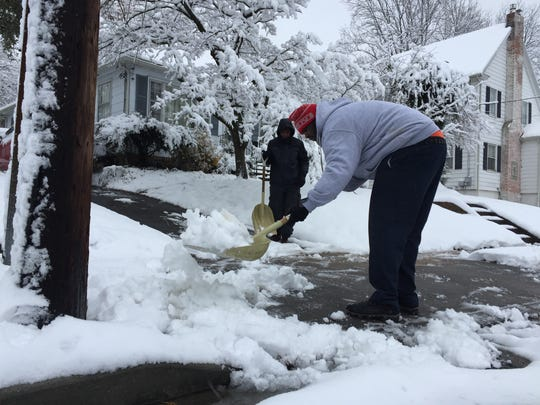 Kevin Tatum tosses a shovel full of snow Saturday, Dec. 9, near his home on Lakeside Drive in Salisbury as his son, Ondre, looks on.