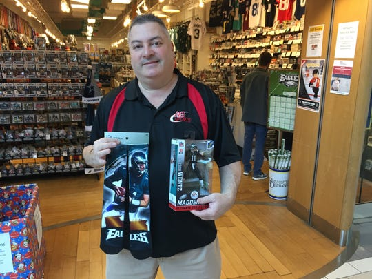 AB Sports co-owner Scott Polsen holds Carson Wentz memorabilia outside his store at the Concord Mall Monday.