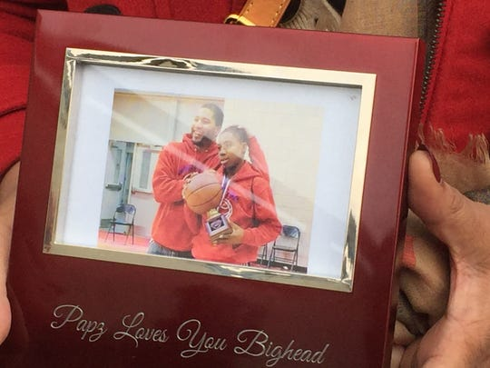 Linda High holds a photo of her son James High, pictured left, with her grandson. James High was murdered in July 2015 outside the Antler Lodge in Binghamton.