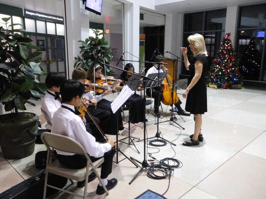 Lisa Pettit directs Deerlake orchestra students during the Winter Festival reception.