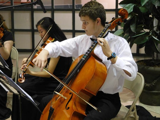 Violist Madeline McNally plays next to cellist Luke