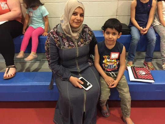 Amani Asfour (left) sits with her son, Wisam Abu-HJaze (right), during his kindergarten orientation. Abu-HJaze attends school in the Chambersburg Area School District.