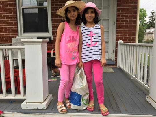 Sham Abu-HJaze (left) poses for a photo with her sister, Fagar Abu-HJaze (right) on the front porch of their house in Chambersburg.